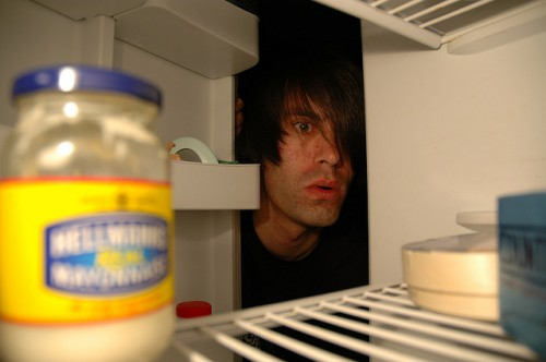 a picture of a man looking inside a fridge